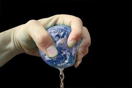 Main pressant la Terre de laquelle coule un liquide