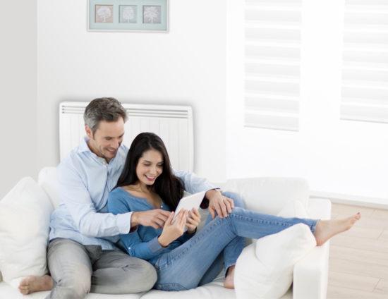 Couple sur un canapé devant un radiateur électrique.