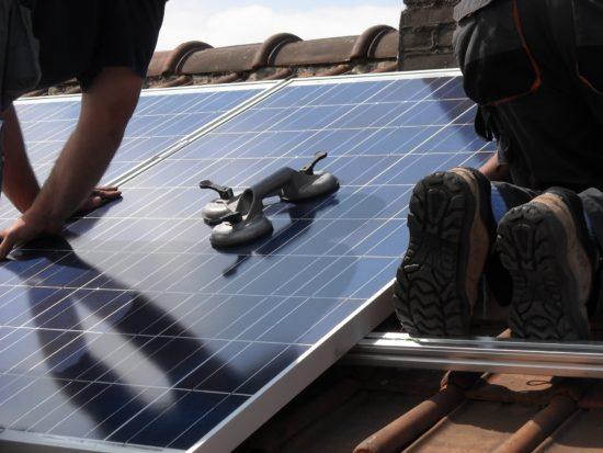 Installation de panneaux solaires sur le toit d'une maison.