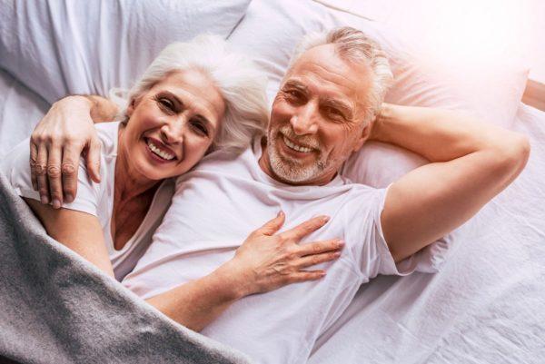 couple senior souriant dans un lit